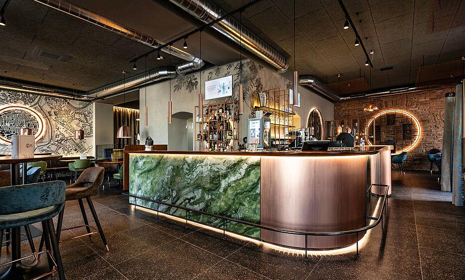 Bar und Cafe Einrichtung von der id Werkstatt - Barfront aus Stein mit ind. Beleuchtung, darüber Nussmassivholz als Bar Pult, dazu kombiniert Kupfer, Tapeten und viel Samtstoff