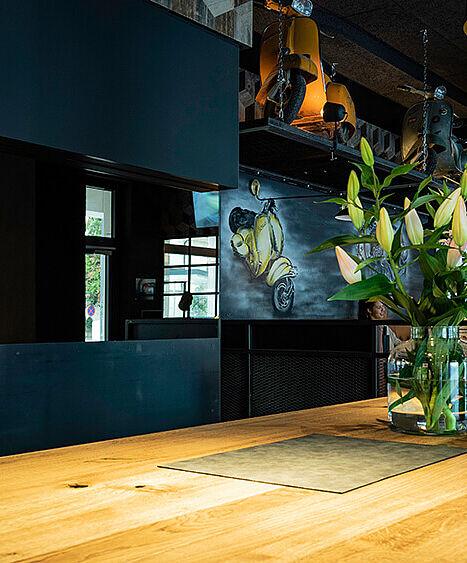 """ID-Werkstatt Referenz """"Flax"""" in Feldkirch. Restaurant Ausstattung, Service Anrichte in Eiche, darauf Vase mit Blumen. Im Hintergrund Messing Hängelampe und Wandmalerei mit Vespa Motiv."""