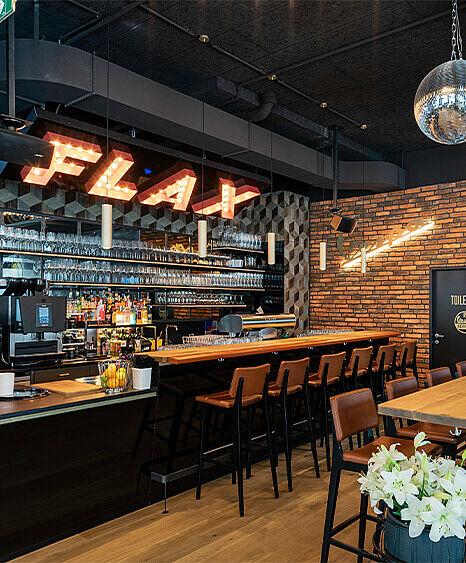Restaurant Einrichtung Flax in Feldkirch, Voralberg, Bargestaltung mit Eiche und Stahl inklusive Beleuchtungskonzept mit Glühbirnen durch die id-Werkstatt