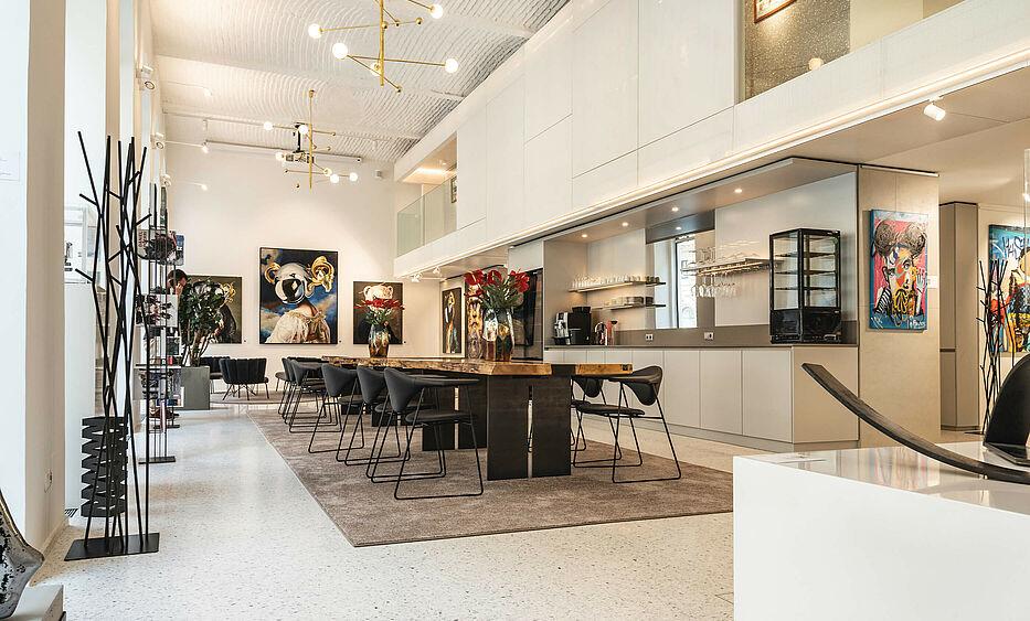 Galerieeinrichtung, Interior Design von der id Werkstatt, Massivholzstammtische mit einer Umgebung von außergewöhnlichen Kunstwerken.