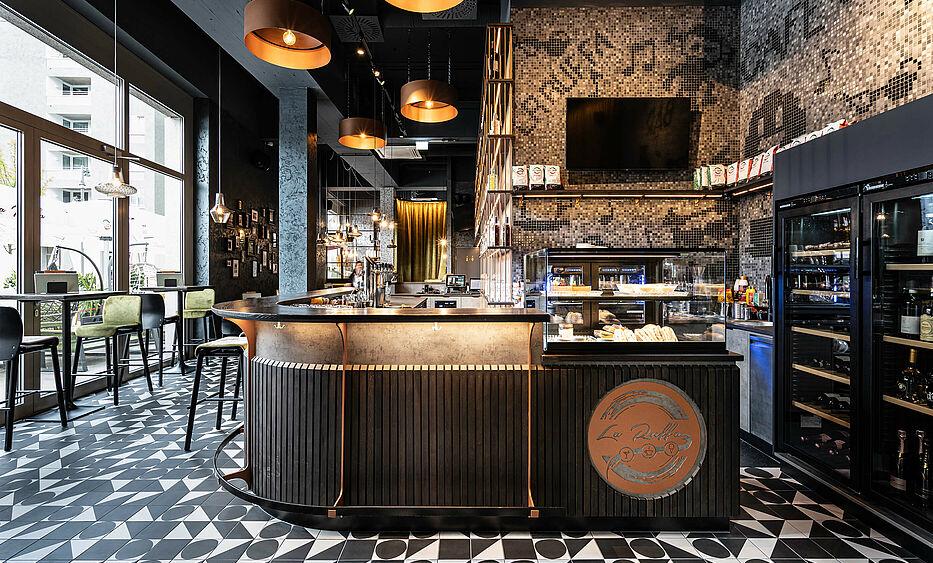 Bar- und Cafeeinrichtung von der id Werkstatt aus Vorchdorf, Eckbar mit Holzlamellen und Betonoptik Brfront, darüber Barpult aus Eichenmassivholz