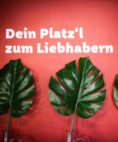 """Restaurant Einrichtung - Liebhaberei Linz, Wandgestaltung mit Spruch: """"Dein Platz'l zum Liebhabern"""" und davor Dekoration - ID-Werkstatt, Gastronomie Einrichtung aus Österreich"""