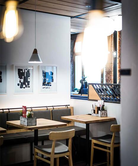 Selbstbedienungsrestaurant - Liebhaberei Linz, Hochsitzbereich mit Pendellampen und Bildern - ID-Werkstatt, Innenarchitektur aus Österreich