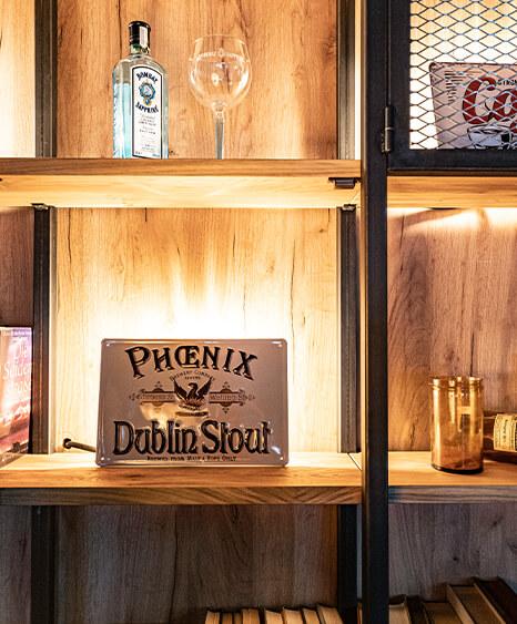 Restauranteinrichtung in Rohrbach, Wandgestaltung durch Formrohrregal mit Eicheneinlägeböden, darauf verschieden Dekorationsartikel wie Alkoholische Glasflaschen und Blechschilder durch die id Werkstatt.