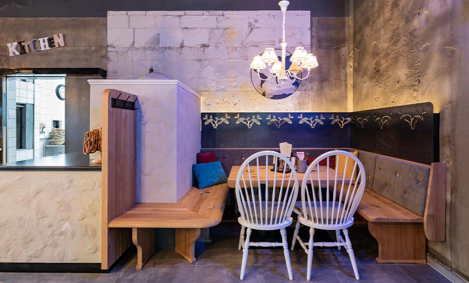 Interior Design - bei id Werkstatt. Stammtisch mit Kachelofen und Stoff Lampenschirm, ebenfalls mit Muster gelasertes Stahl an Wand montiert.