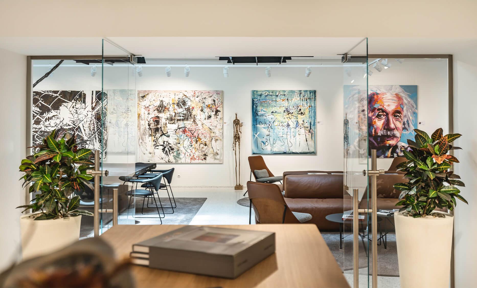 Lounge und Konferenzraum, Interior Design von der id Werkstatt, Sattelbraune Leder Sofas mittig platziert, rundherum Kunstvolle Bilder von verschiedenen Künstlern, Pflanzen, Akustikpanele und Teppich verleihen eine gemütliche Atmosphäre