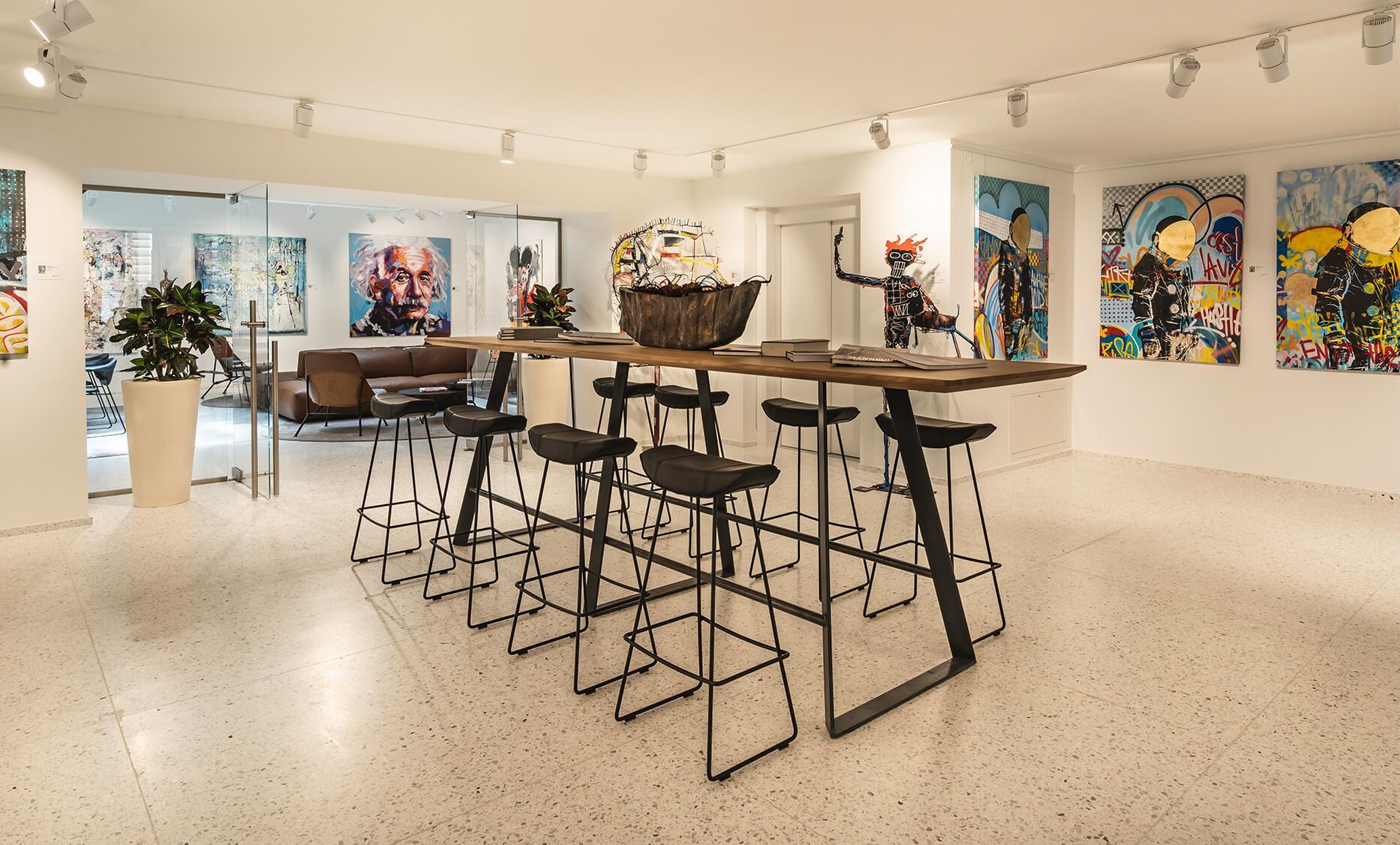 Einrichtung und Möbel von der id Werkstatt, Hochbereich mit Kuffen Metallgestell, Massivholzplatte Eiche, Hochsitzer im Reitersattel design von Freifrau, umgeben von viel Kunst