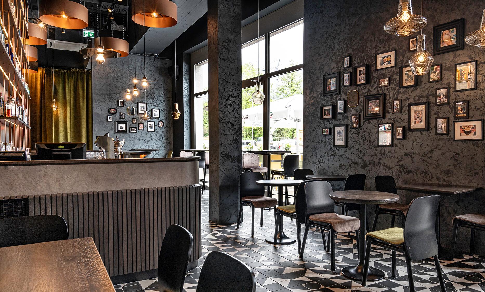 Gastronomieeinrichtung von der id Werkstatt aus Vorchdorf, Sitzbereich mit gemütlich grün tapezierten Stühlen auf einem schwarz-weiß gemusterten Fliesenboden, an der Decke Spiegellampen mit Kupfereinfassung