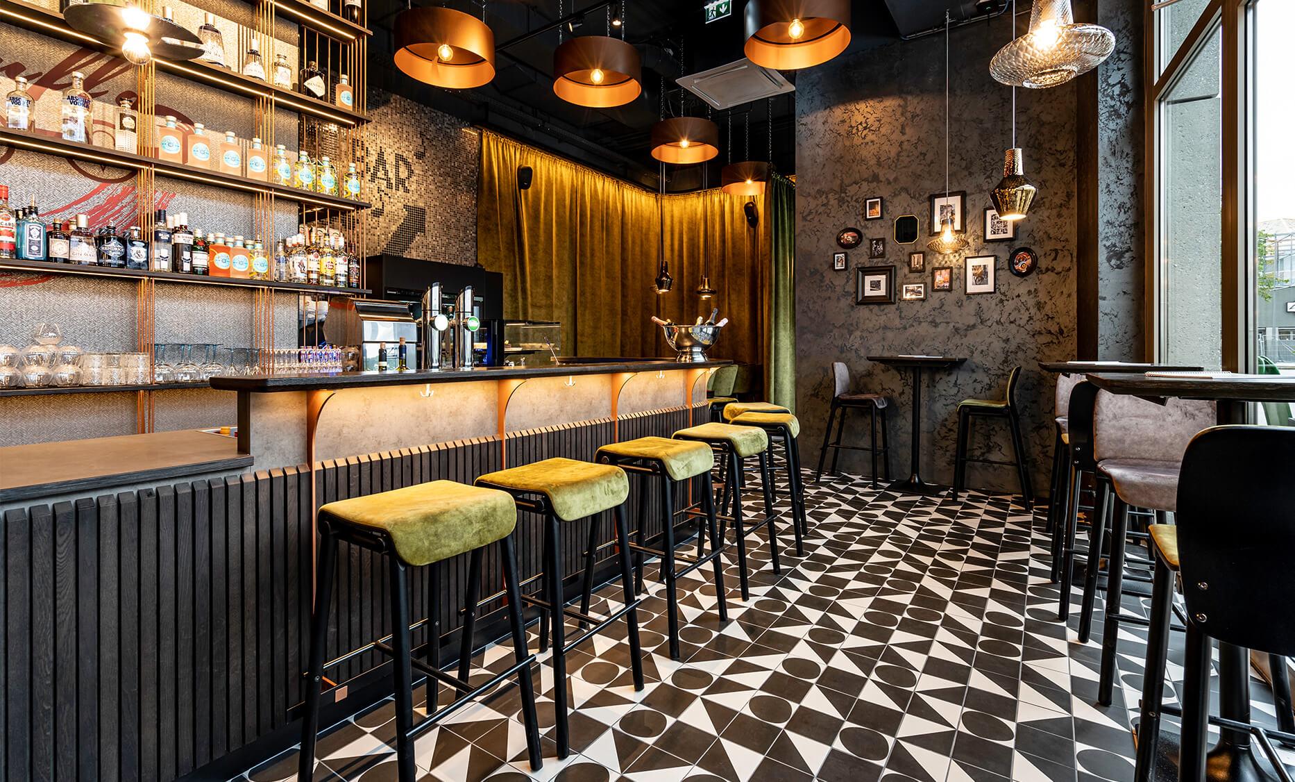 Bar Interior Design von der id Werkstatt aus Vorchdorf, Bar und Hochbereich, dahinter gemütliche Sitzecke umrahmt mit flauschigen Vorhängen, dekoratives Licht mittels Glasschirmchen