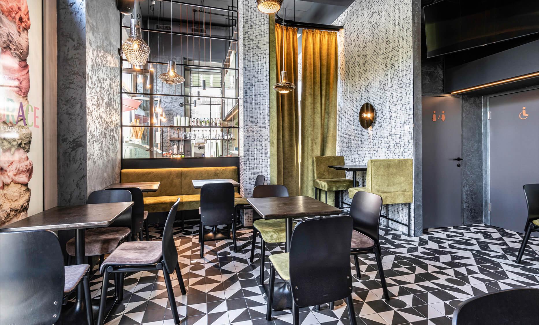 Hinterer Sitzbereich des Cafe Bar La Ruffa Lokales in Linz-Oed mit Vorhängen, bunten Fliesen und Masssivholztischen von der id Werkstatt aus Vorchdorf