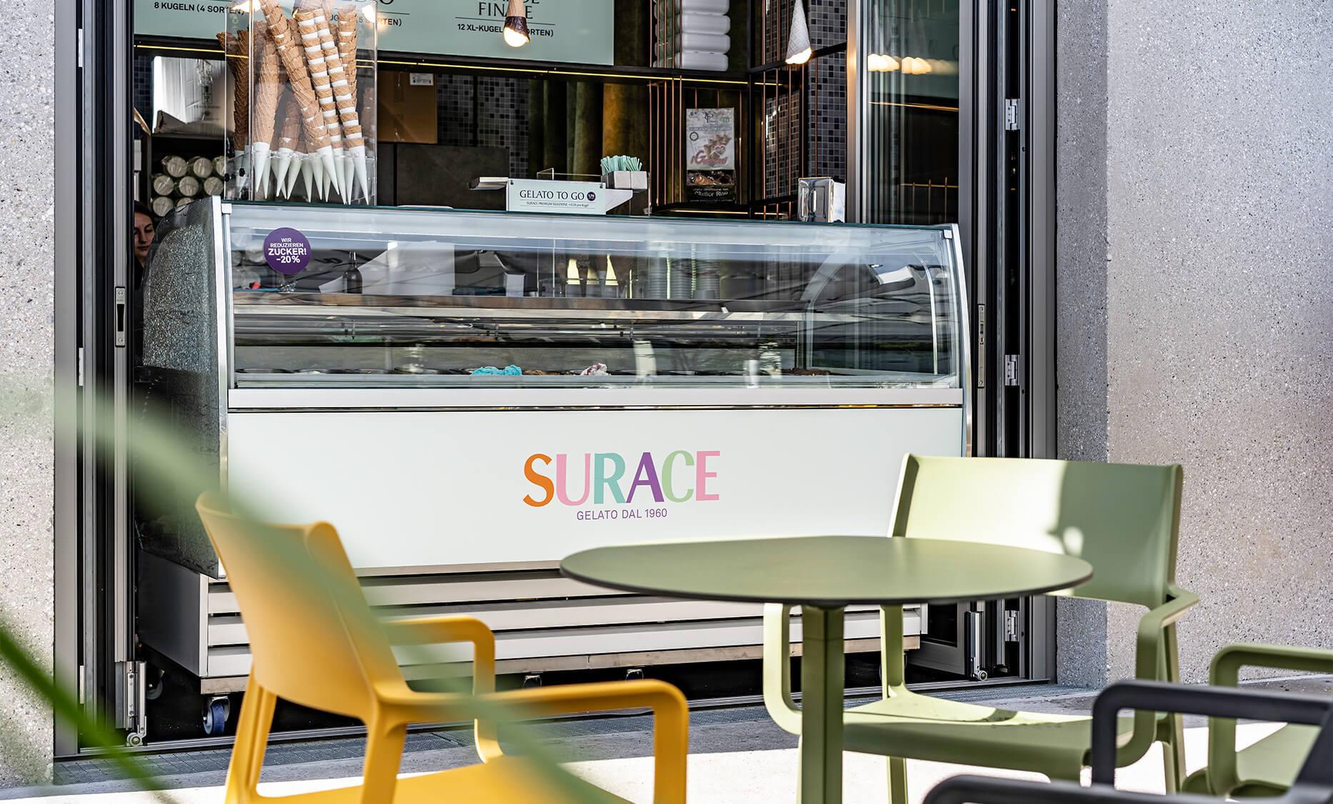 Gelateria oder Cafe Bar in Linz-Oed, Interior Design von der id Werkstatt aus Vorchdorf, Eisvitrine mit bunten Eissorten, darüber Metallstäberegal und Eistüten Lampen