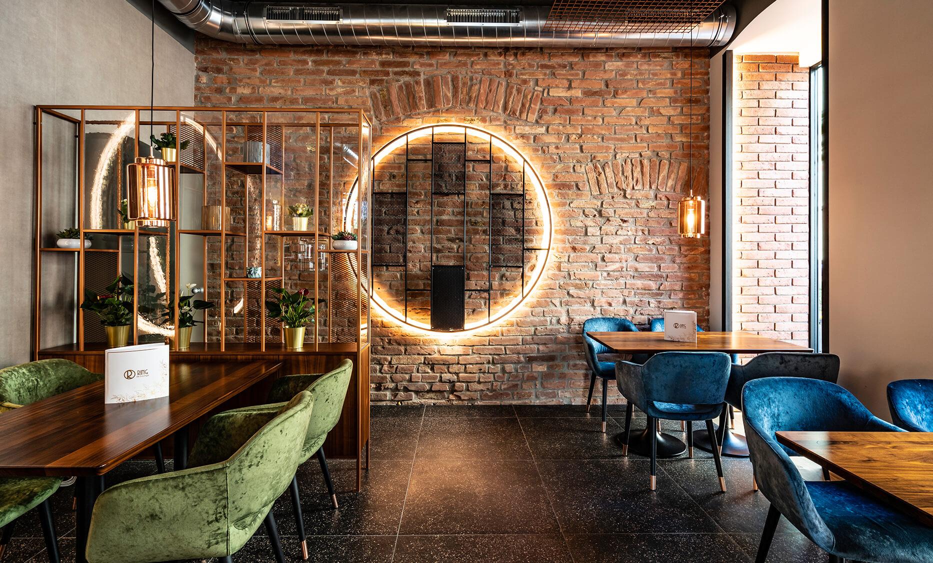 Alte Ziegelmauer wiederaufgearbeitet, davor Ring aus Stahl Formrohr mit indirekter Beleuchtung - Interior Design by id Werkstatt