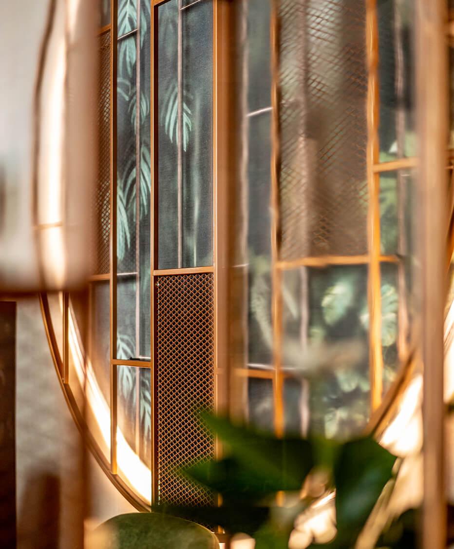 Detailfoto vom Lokal Ring de Lounge in Wien - Formrohrregal Kupferfärbig lackiert, kombiniert mit Industrie Glasfüllungen und einer Floral Tapete als Auflockerung - Planung und Umsetzung von den Gastroeinrichtern der id Werkstatt