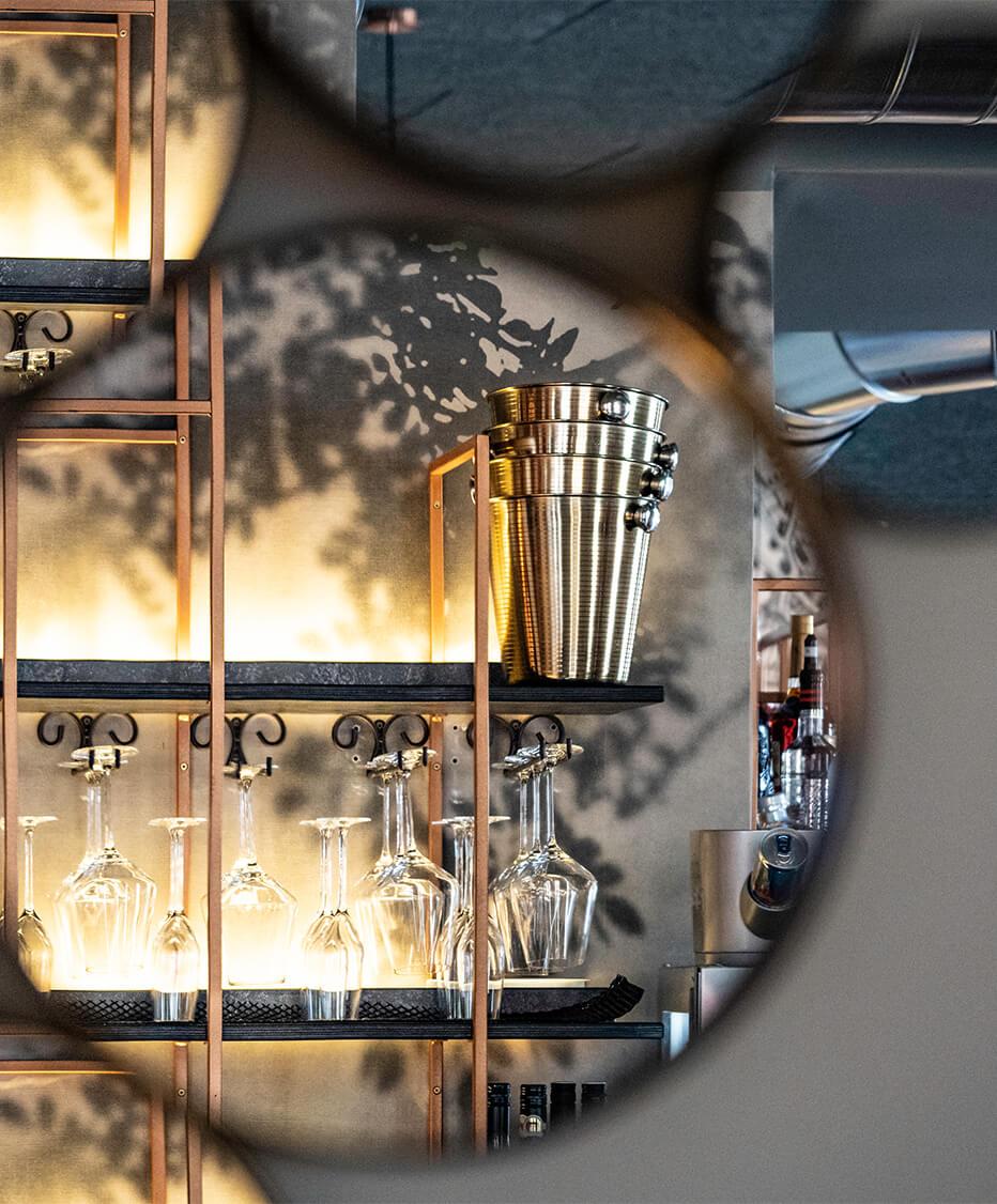 Detailfoto - Barrückwand spiegelt sich in den runden Dekospiegeln an der Wand. Indirekte Beleuchtung der Gläser und Flaschen im Kupferfärbigen Formrohregal - dahinter Floral Tapete mit grauem Farbstich
