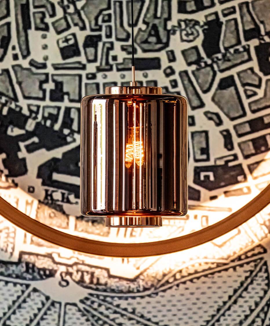 Beleuchtungskonzept und Einrichtung von der id Werkstatt aus Vorchdorf - Kupferfärbige Glas Pendellampen mit warmen gemütlichen Licht. Dahinter Tapete mit dem Motiv der Wiener Ringstraße