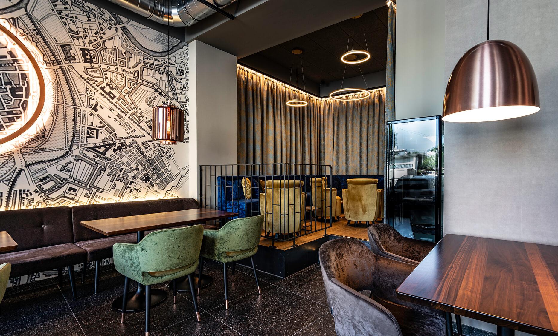 Sitz und Lounge Bereich vom Cafe Ring de Lounge in Wien - Vorhang mit Samtstoff, davor gemütliche Sofabänke in Royalblau. Boden Terrazzofliesen in schwarz matt, Lounge Bereich mit warmen Eichenboden
