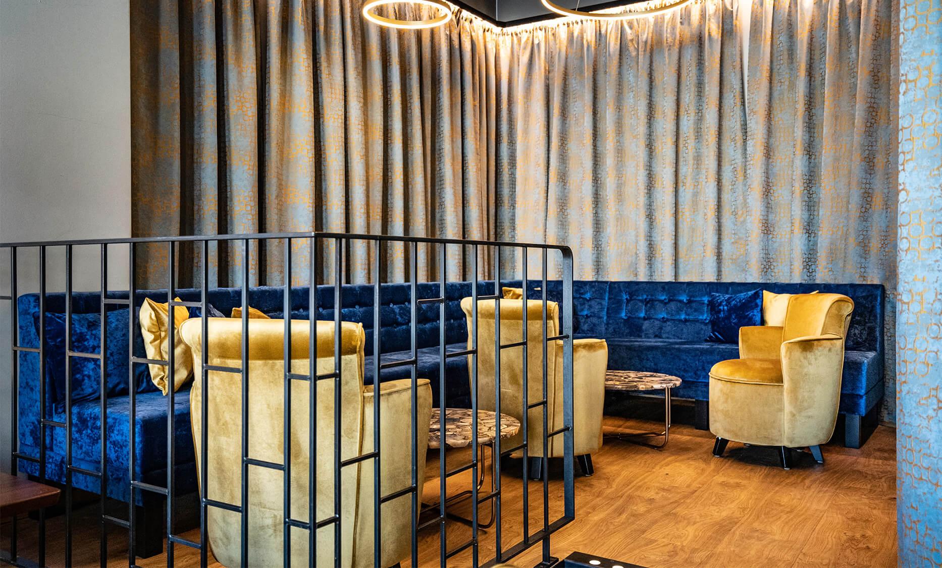Ring de Lounge in Wien - Lounge Bereich mit gemütlichen kleinen Sitzhockern umrahmt mit einer Royalblauen Sofa Bank. Leuchtringe an der Decke sowie die indirekte Beleuchtung des Vorhangs verleihen der Lounge eine gemütliche Atmosphäre. Einrichtung von der id Werkstatt